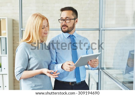 Young manager talking to female chief - stock photo
