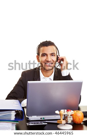 Young manager using a laptop with a headset