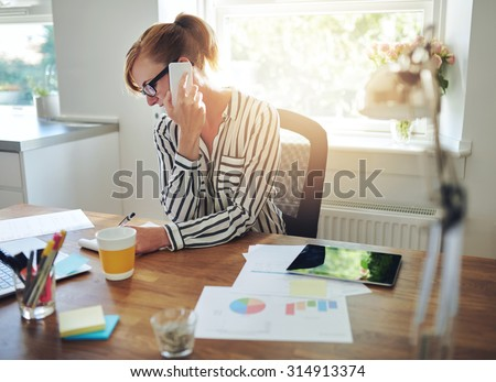 Young manageress working at her desk in the office taking a call on her mobile phone while writing notes on a notepad, charts and graphs in the foreground - stock photo