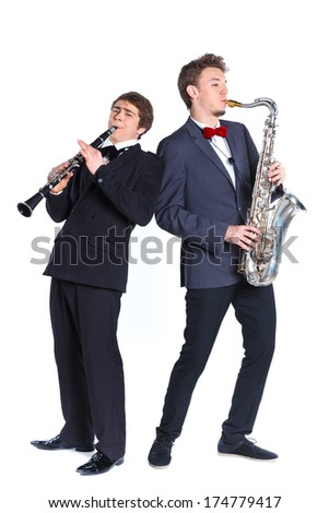 Young mans in a suit playing on saxophone and clarinet. Isolated on background