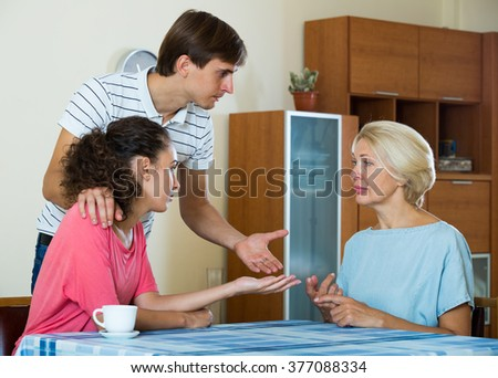 Young married couple and senior mother having bad discussion