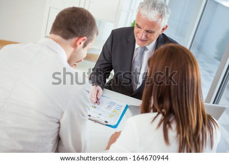 Young married couple at the financial advisor. - stock photo