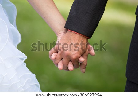 Young married couple holding hands, ceremony wedding day - stock photo