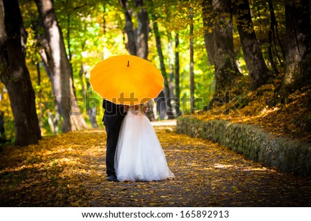 Young married couple in love kissing under umbrella in side a forest park autumn