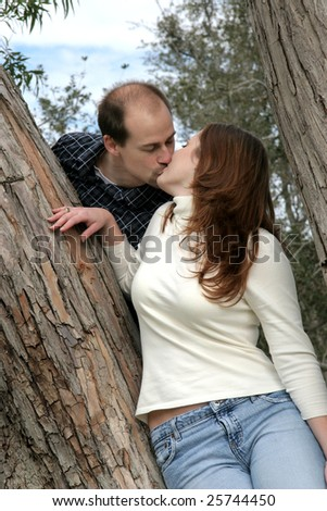 young married couple kiss in a tree - stock photo