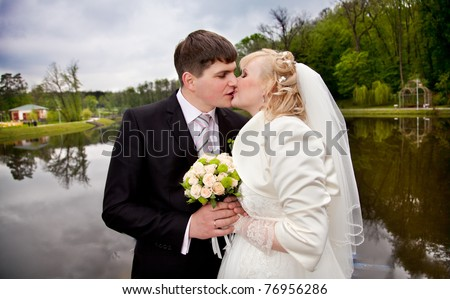 Young married couple kissing near lake