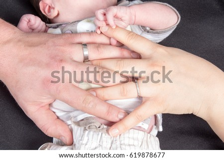 young married couple lay their hands with the wedding rings on the belly of their newborn baby
