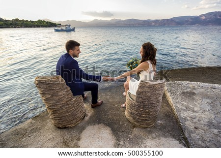 Young married couple sitting on chairs made of palm tree trunk, holding hands and looking at each other.