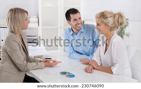 Young married couple sitting with an adviser at desk in a guidance or professional business meeting planning their provision for one's old age. - stock photo
