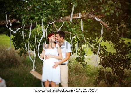 Young married couple walking in the park. Young beautiful pregnant woman hugging her husband.