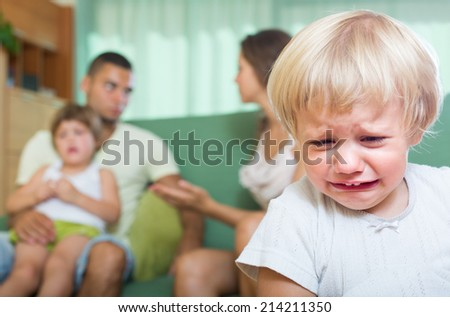 Young married couple with two little daughters having quarrel at home  - stock photo