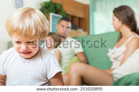 Young married couple with two little daughters having quarrel in the living room  - stock photo