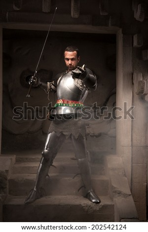 Young masculine man in historical costume. Medieval warrior with armor and sword reaching out on steps of ancient temple, dark - stock photo