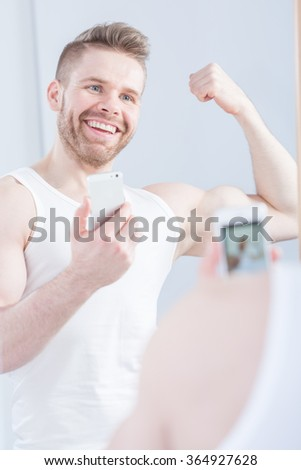 Young masculine man is stretching his bicep to selfie - stock photo