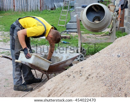 Young mason is taking grout or mortar with trowel from wheelbarrow.         - stock photo