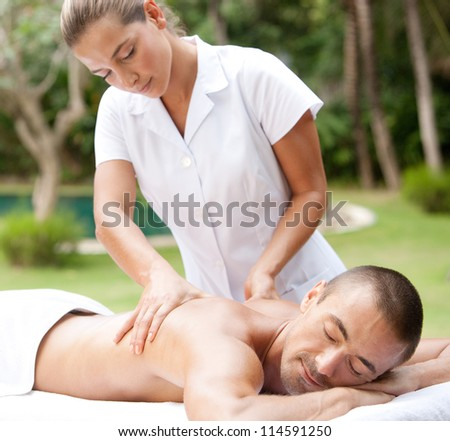 Young masseuse massaging an attractive man in a tropical hotel garden near a swimming pool. - stock photo