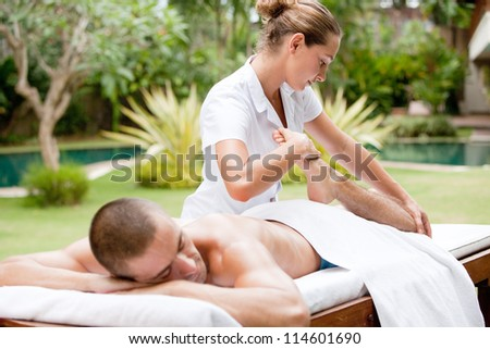 Young masseuse massaging and stretching the body of an attractive man in a tropical hotel garden near a swimming pool. - stock photo