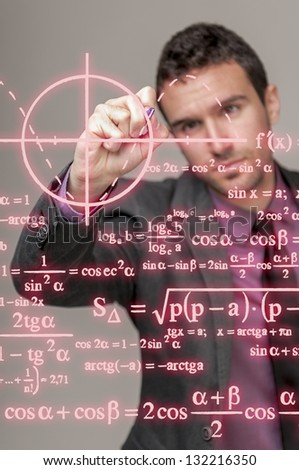 Young mathematician writing on a transparent board - stock photo