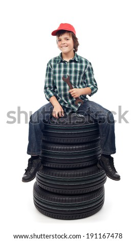 Young mechanic boy sitting on new car tires holding wrench - isolated - stock photo