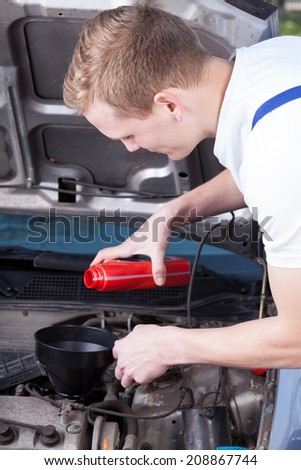 Young mechanic changing car oil in focus  - stock photo
