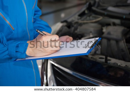 Young mechanic engineer taking a note on clipboard for examining a vehicle.. - stock photo