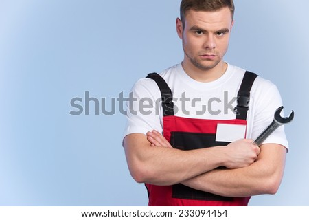 Young mechanic in red overall standing against blue background. serious man holding spanner and looking into camera - stock photo
