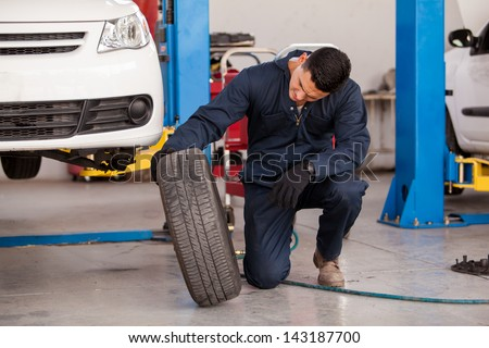 Young mechanic inspecting a car tire at an auto shop - stock photo