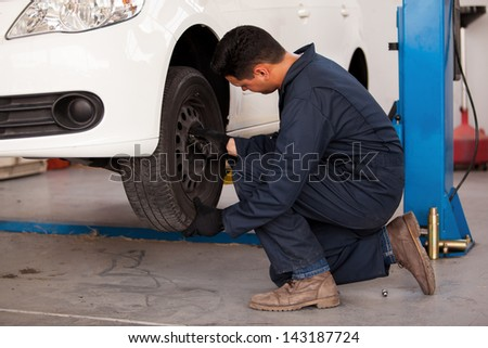 Young mechanic rotating tires of a suspended car at an auto shop - stock photo