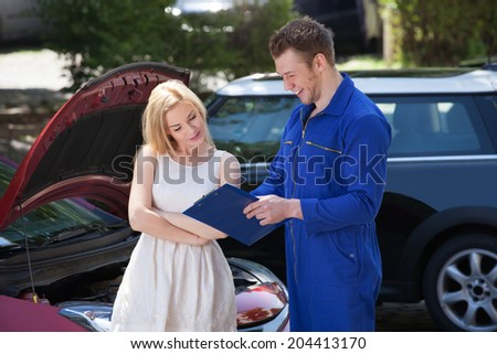Young mechanic showing clipboard to female customer by breakdown car - stock photo