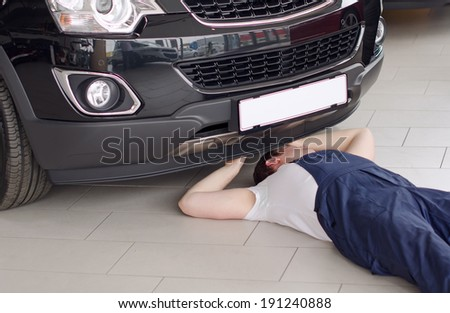 Young mechanic under car in service center. - stock photo