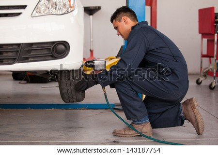 Young mechanic using an air gun to tighten a tire bolts on a suspended car at an auto shop - stock photo
