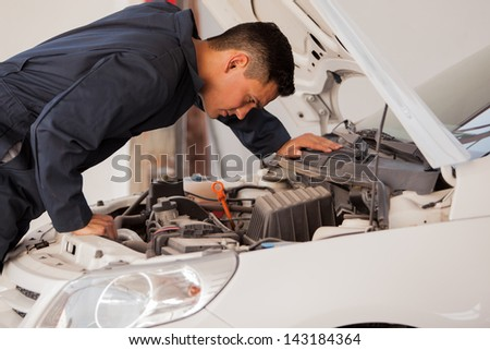 Young mechanic wearing an overall inspecting an engine at an auto shop - stock photo