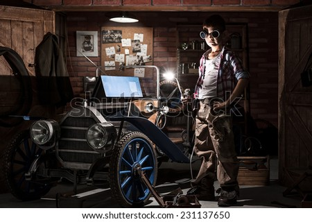 Young mechanic with a welder in a retro car in the garage at night - stock photo