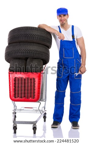 young mechanic with full shopping carts of new  tires car - stock photo