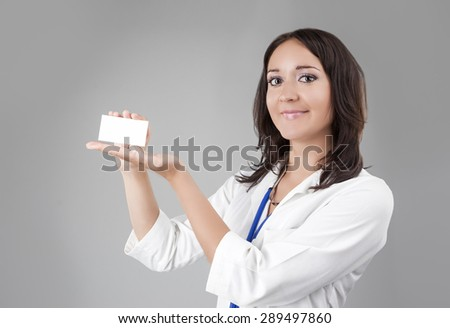 Young Medical Female Doctor Presenting and Showing White Card for Product or Text. Caucasian Medical Professional Staff Posing Against Gray. Horizontal Image - stock photo