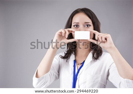 Young Medical Female Doctor Presenting and Showing White Card In Front of Mouth for Product or Text. Caucasian Medical Professional Staff Posing Against Gray. Horizontal Image - stock photo