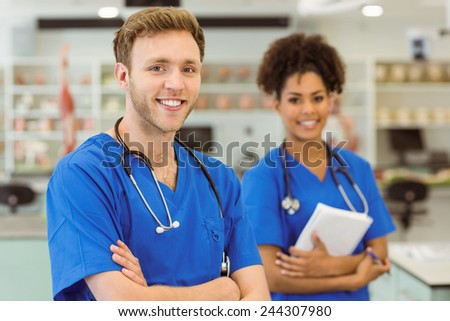 Young medical students smiling at the camera at the university - stock photo