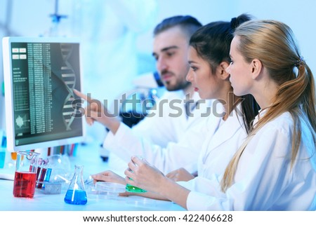 Young medical technicians working in laboratory - stock photo