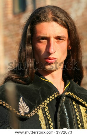 Young medieval blade-smith sword-cutler prince with black mantle - stock photo