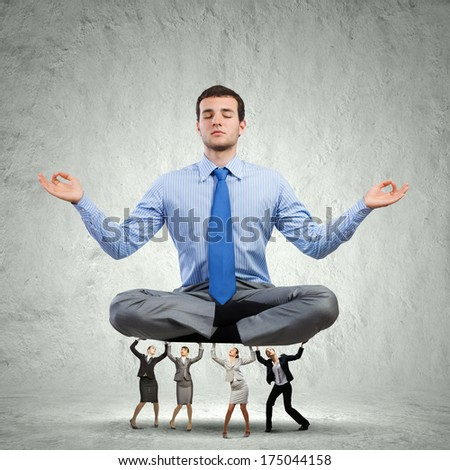 Young meditating businessman supported by business colleagues
