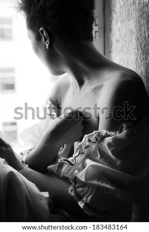 Young melancholy and sad woman looking through the window - stock photo