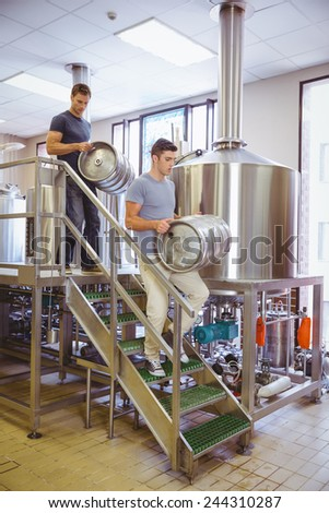 Young men carrying keg smiling at camera in the factory