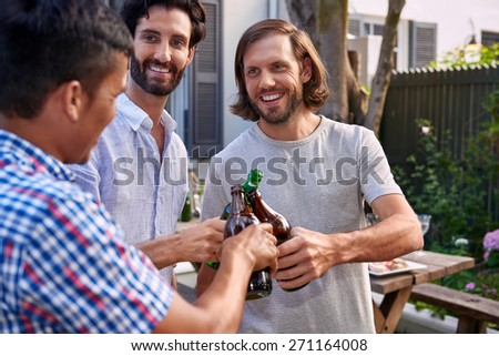 young men cheers toasting alcoholic beer bottles at outdoor garden party - stock photo