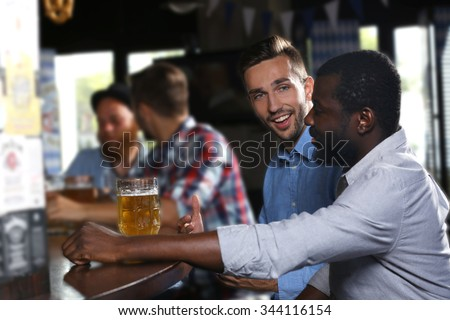 Young men drinking beer in pub - stock photo