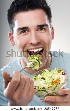 young men eating salad close up shoot - stock photo