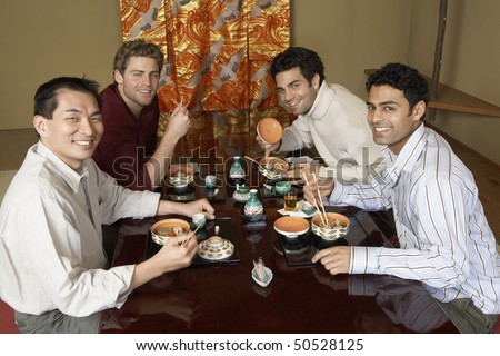 Young men eating sushi with chopsticks in restaurant - stock photo