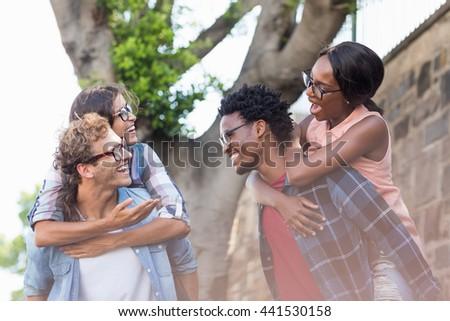 Young men giving piggyback to women outdoors - stock photo