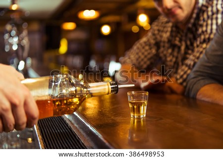 Young men in casual clothes is sitting at bar counter in pub, a bartender is pouring alcoholic beverage into glass, close-up