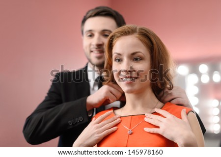 Young men in full suit helping to put on the necklace on his girlfriend - stock photo