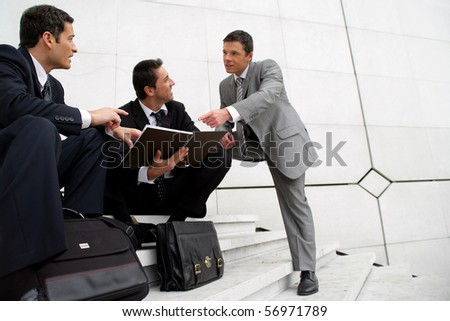 Young men in suit sitting on steps of stairs - stock photo